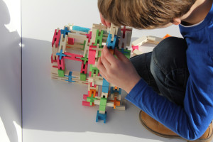 boy playing with wooden block toys from luco toy